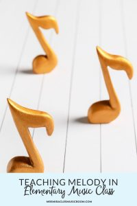 """Three music notes on a wooden floor, with the text, """"Teaching melody in elementary music class"""""""